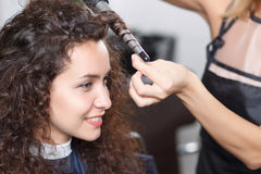 Nice hairdresser holding curling Stock Images