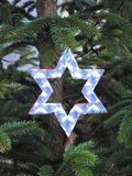 Handmade white shining star hanging on Christmas tree Royalty Free Stock Photography