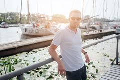 Nice and handsome guy stand on pier and lean to railing. He looks on camera. Guy is confident. He wears white shirt and. Black shorts stock images