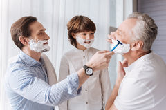 Nice handsome man helping his father to shave. Do you need help. Nice handsome positive men holding a razor and looking at his father while helping him to shave Royalty Free Stock Images