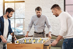 Nice handsome men standing opposite each other. Focused on the game. Nice handsome pleasant men standing opposite each other and looking at the field while royalty free stock photo