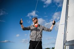 Nice happy bearded man sailor thumbing up and evincing positivity while at his yacht or boat on a river or sea. Nice happy bearded man sailor thumbing up and royalty free stock photos