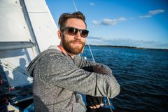 Nice happy bearded man sailor thumbing up and evincing positivity while at his yacht or boat on a river or sea. Nice happy bearded man sailor thumbing up and royalty free stock photo