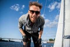 Nice happy bearded man sailor thumbing up and evincing positivity while at his yacht or boat on a river or sea. Nice happy bearded man sailor thumbing up and royalty free stock photography