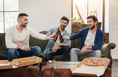 Nice happy friends cheering with beer. Cheers for us. Nice happy male friends holding bottles of beer and cheering with them while sitting on the sofa Royalty Free Stock Images