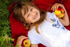 Happy little blonde girl with red apples, close-up.On the background of green grass. stock photo