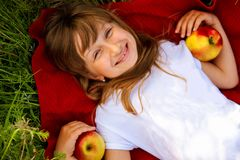 Nice happy little blonde girl with red apples, close-up.On the background of green grass. stock photos