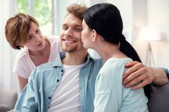 Nice happy man smiling. Pleasant kiss. Nice happy men smiling while being kissed by his wife stock photo