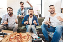 Nice happy men supporting their football team. Watching a football match. Nice happy delighted men watching TV and drinking beer while being happy for their stock images
