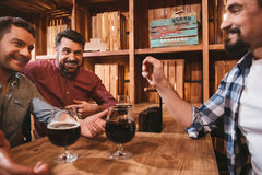Nice happy men talking with each other. Pleasant communication. Nice happy pleasant men sitting together and drinking beer while talking to each other royalty free stock photos