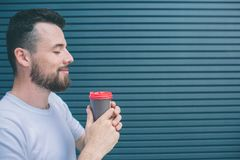 Nice and happy person is holding cup of coffee witht both hands. He is smiling. Guy is keeping eyes closed. Isolated on. Striped and blue background stock image