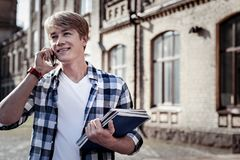 Nice happy student talking on the phone. Mobile communication. Nice happy male student talking on the phone and smiling while holding his manuals Royalty Free Stock Photo