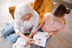 Nice happy woman looking at her granddaughters embroidery Stock Photos