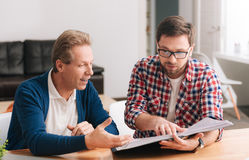 Nice hard working men looking at the folder with documents. Working on a project. Nice hard working pleasant men looking at the folder with documents and royalty free stock images