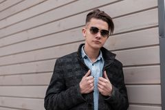 Nice hipster young man in a stylish plaid jacket in a classic shirt in fashionable sunglasses with a trendy hairstyle poses. Near a wooden building on the royalty free stock photography