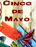 Nice image for Cinco de Mayo, a Mexican celebration, on the 5th of May. Red, green and gold beads with Mexican flag and red chilis on a wooden background royalty free stock photo