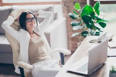 Nice, independent, cute woman in white suit, formal wear, glasse. S sitting on chair at her desk in office, holding arms behind the head with close eyes Stock Image