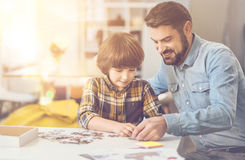 Nice intelligent boy doing a jigsaw puzzle with his father. Time together. Nice intelligent positive boy sitting at the table and doing a jigsaw puzzle while Royalty Free Stock Photo