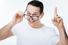 Nice intelligent man having an idea. Bright idea. Nice positive intelligent man pointing up with his finger and smiling while having a creative idea Stock Images