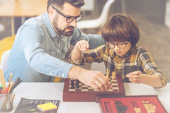 Nice intelligent man teaching his son to play chess. Intellectual games. Nice intelligent positive men sitting with his son and teaching him how to play chess Stock Image