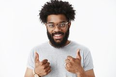 Nice job, proud of you. Portrait of satisfied supportive and friendly male entrepreneur with beard, pierced nose and. Afro hairstyle showing thumbs up gesture stock image