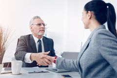 Cheerful boss and female office worker shaking hands. Nice job. Selective focus on a positive minded chief looking at his young up and coming employee with a royalty free stock photo