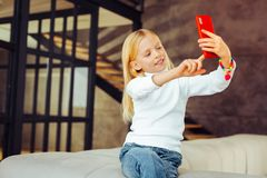 Nice joke. Attractive kid expressing positivity while looking aside. Jewelry for kids. Attentive preschooler demonstrating her smile while doing selfie stock images