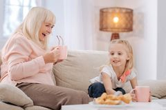 Nice joyful grandmother having tea with her granddaughter. Afternoon tea. Joyful delighted nice grandmother sitting on the sofa and smiling while having tea with Royalty Free Stock Photo