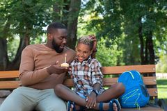 Nice joyful man congratulating his son on birthday. Festive mood. Nice joyful men congratulating his son while sitting with his on the bench royalty free stock photo