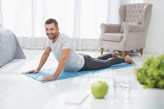 Nice joyful man doing push ups. In shape. Nice joyful man lying on the floor while doing push ups Royalty Free Stock Photos