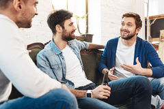 Nice joyful men chatting with each other. Communication with friends. Nice joyful positive men laughing and chatting with each other while having a great time stock photography