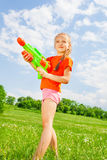 Nice kid girl with a water gun. Beautiful girl stands with a water gun on a grassy dandelion meadow royalty free stock photos