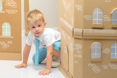 A little boy is playing in a cardboard house. royalty free stock image