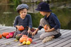 Nice kids paint small Halloween pumpkins. On the river bank Royalty Free Stock Photography