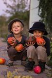 Nice kids sitting with Halloween pumpkins Royalty Free Stock Photography