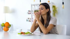 Nice lady praying, blessing God for dinner, eating healthy vegetarian salad. Stock photo royalty free stock photos