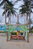 Mother and daughter sit on the bench with nice bed, coconut and the beach royalty free stock photo
