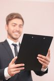 Nice lawyer holding papers. Happy at work. Selective focus of folder in hands of smiling handsome lawyer holding it royalty free stock photography