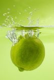 Nice lime falling into water. Green background. Stock Images