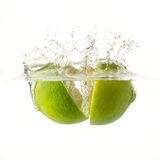 Nice lime falling into water. White background. Ripe lime falling into water, splashes all around Stock Photos