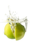 Nice lime falling into water. White background. Ripe lime falling into water, splashes all around Royalty Free Stock Photo