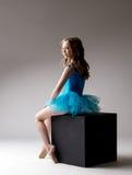 Nice little ballerina posing on cube in studio Stock Images