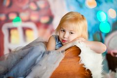 Nice little blonde sad girl siting in the toy sledge with white stock photos