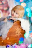 Nice little blonde sad girl siting in the toy sledge with white fur. Christmas and New Year theme royalty free stock photo