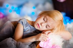 Nice little blonde sleeping girl siting in the toy sledge with w royalty free stock photo