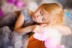 Nice little blonde sleeping girl siting in the toy sledge with white fur. Christmas and New Year theme stock photography