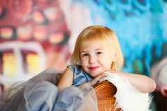 Nice little blonde smiling girl siting in the toy sledge with white fur. Christmas and New Year theme stock photography