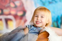 Nice little blonde smiling girl siting in the toy sledge with white fur. Christmas and New Year theme stock image