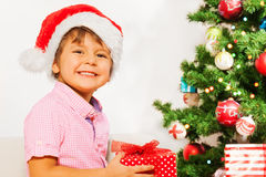 Nice little boy in Santa hat with present smiling Stock Photo