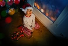 Little boy with lights garland near Christmas tree Royalty Free Stock Image